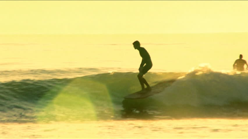 A surfer on a longboard performs turns and tricks during sunset - HD stock video clip