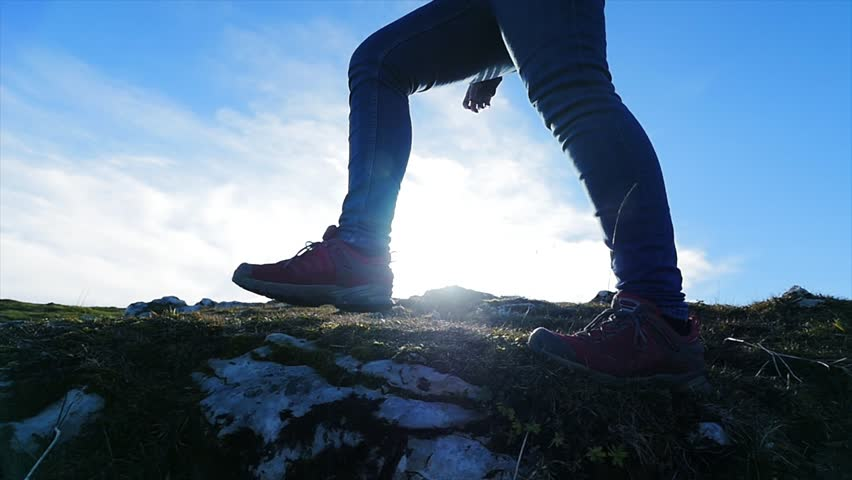 feet walking over rocky terrain. hiker hiking outdoors. foot steps background