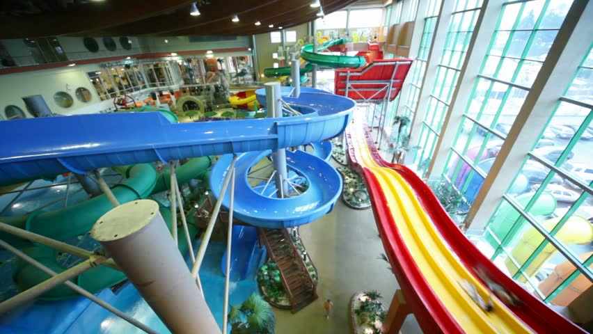 People Rapidly Slide Down A Wet Red And Blue Plastic Hills In Large Indoor Water Park ...