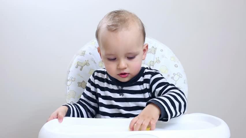 Adorable baby boy eating lemon