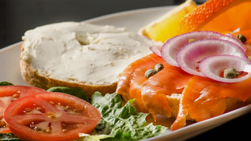 Open face smoked salmon sandwich with cream cheese,chives,onions and a garnish of lettuce,tomato,oranges - 4K stock video clip