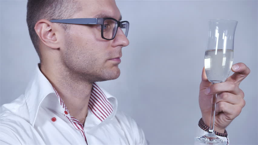 Close up of a young elegant businessman wearing a white shirt and eye glasses drinking champagne. Studio shot. - HD stock footage clip