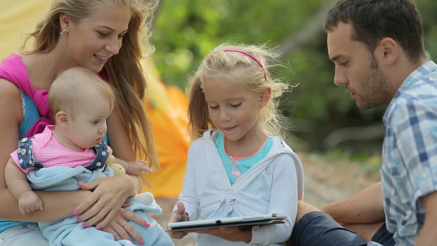Little girl studying tablet on a picnic with her family in the forest - HD stock video clip