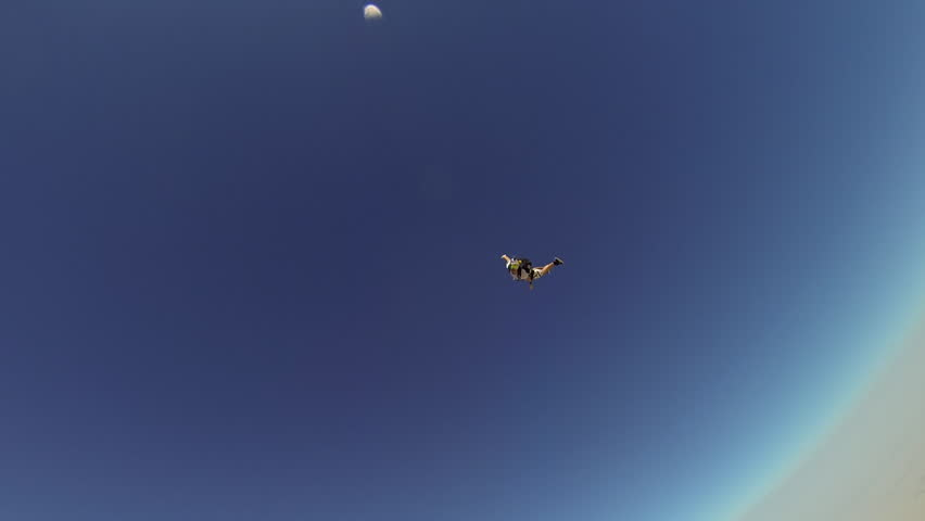 Two skydivers skydiving in the sky, one skydiver holds onto the other while skydiving, POV - HD stock video clip