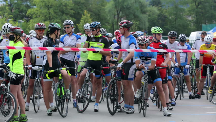 VRHNIKA, SLOVENIA - JUNE 2014: Bicycle group waiting on the start line. Wide shot of competitors on bikes in group talking and waiting for competition. | Shutterstock HD Video #8262352
