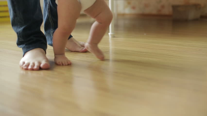 Baby girl ( 1 year old ) walking his first steps, dolly shot