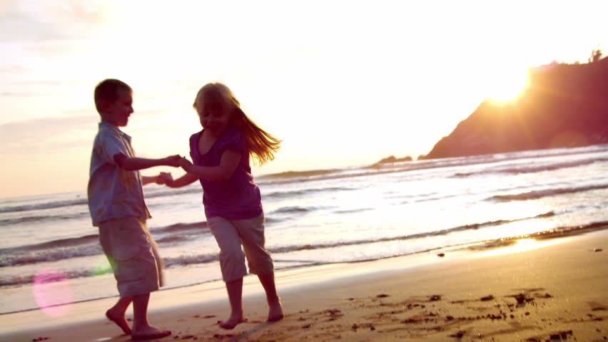 Two children dance on the beach at sunset. lens flare.  | Shutterstock HD Video #827281