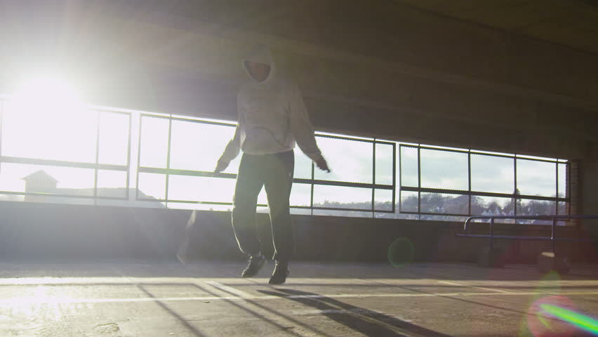 Slow motion tracking shot of a man jump roping in an urban environment during the day with sun flare - 4K stock footage clip