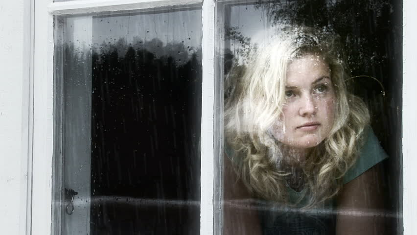Girl looking out of a window a rainy day.