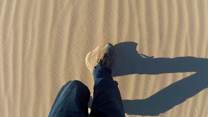 High angle shot of legs and feet of a man walking in a sandy desert. Handheld shot showing hiker and shoes kicking up sand as he shuffles and walks. | Shutterstock HD Video #8336017