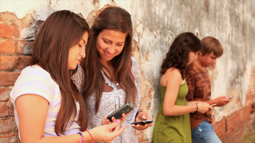 A group of teenagers hanging out by an old brick wall for Hanging groups of pictures