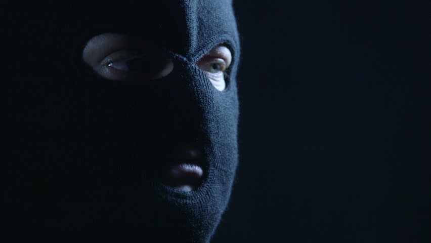 Anonymous person in black balaclava talking to camera