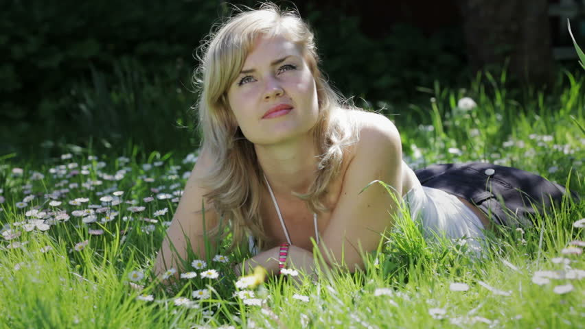 A young blond woman relaxing in grass - HD stock video clip