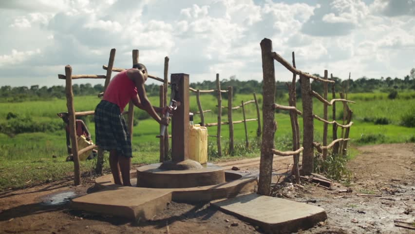 MASINDI, UGANDA - SEPTEMBER 2013: A young African girl fills a water container by a water pump in a rural part of Uganda, Africa