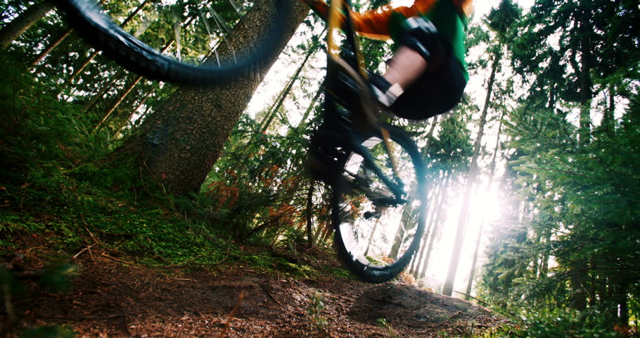 Man on mountain bike jumping ramp with sunflare in 4k slow motion in woods