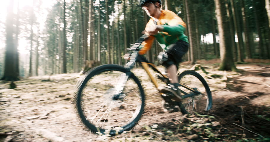 Mountain biker rides downhill on his MTB on track in forest in slow motion