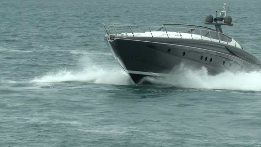 Luxury yacht navigating fast close to the coast
