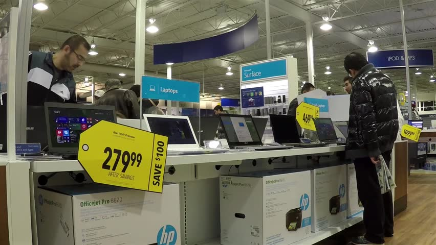 Coquitlam, BC, Canada - December 18, 2014 : People trying apple computer inside Best buy store with wide angle camera shot