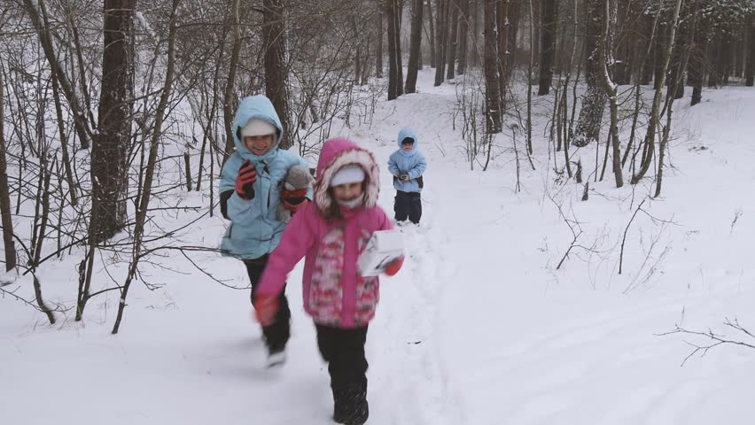 Children running in snow forest, jump and lough. - HD stock footage clip