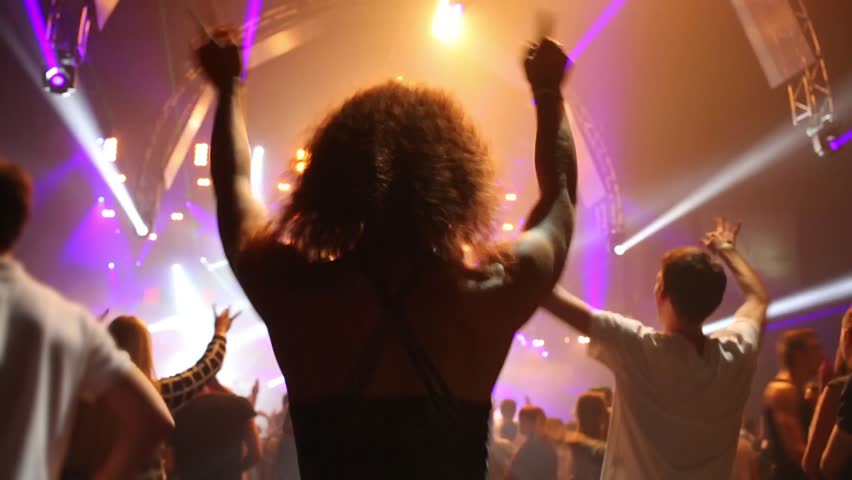 Back of young woman dancing in crowd in night club during big party