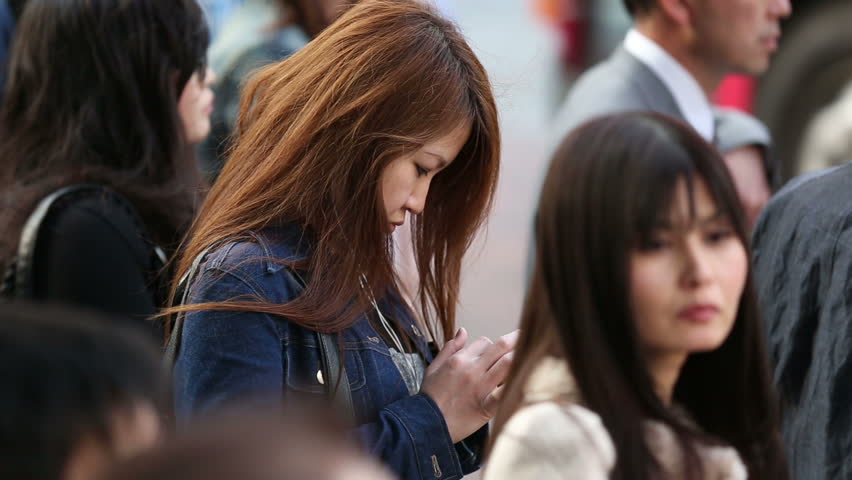 TOKYO, JAPAN - CIRCA 2013: A young female texting while waiting her turn to cross the famous Shibuya intersection  - HD stock video clip