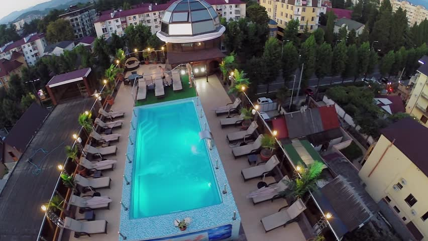 Man walks near pool and woman deeps in water on roof of hotel at summer evening. Aerial view - HD stock footage clip