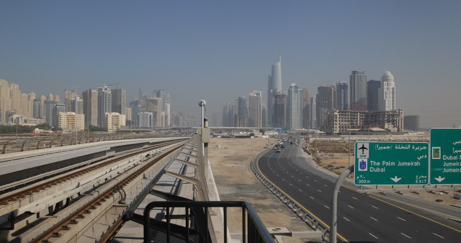 DUBAI, UAE - JANUARY 22, 2014 Dubai Marina Skyline POV Metro Train Arrival Approaching Station Cars Traffic ( Ultra High Definition, UltraHD, Ultra HD, UHD, 4K, 2160P, 4096x2160 )