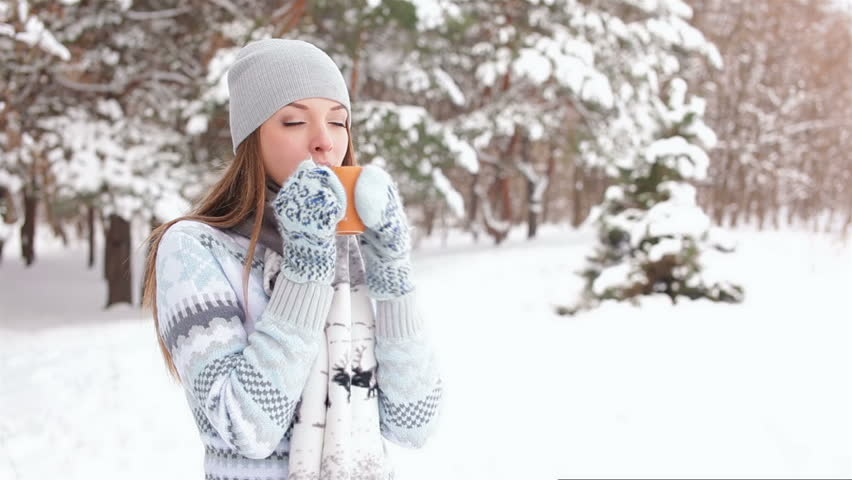 Girl drinks coffee outdoors in winter forest - HD stock video clip