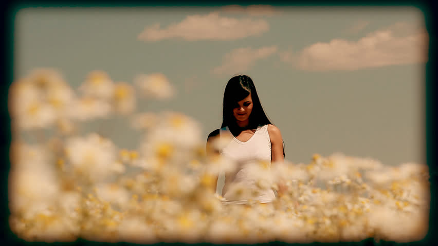 Young woman walking in the meadow, touching camomiles and smiling at camera stylized at reel movie
