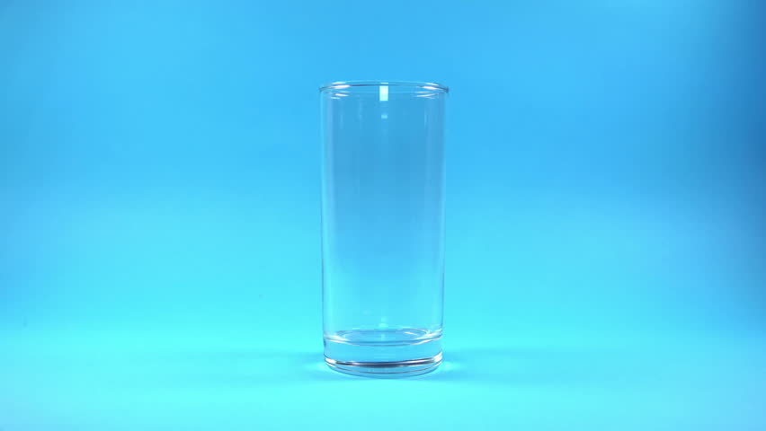 Glass of Milk with Pouring Splash on blue background. 4K Ultra HD 3840x2160 Video Clip