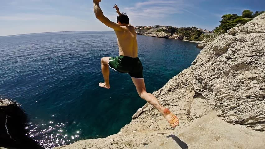 Athletic Young Man Jumping From Cliff Into Ocean Sea Water Muscular Adventure Extreme Sports Lifestyle Hobby Vacation Clear Beach Slow Motion Leisure Activity Gopro HD - HD stock footage clip