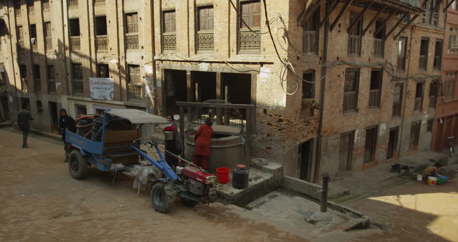 Bhaktapur - March 9 2014: A local Nepali woman gets water from a well. Shot on Red Scarlet. - 4K stock video clip