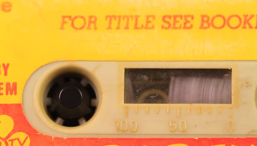 Macro static camera view of vintage audio cassette tape with a yellow label in use playing back in cassette player. All beaten up, faded label colours and dusty. Audio cassette running in tape player