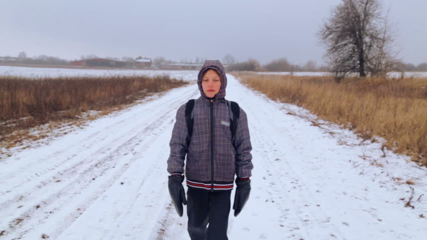 Caucasian boy teenager traveling in winter. The child goes on a winter road through the fields. Purposeful teenager overcomes the hard way.    Shutterstock HD Video #8730019