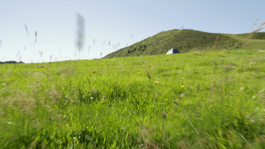 Walking along grass mountain outdoor nature scenery during sunny summer day - establishing gimbal steadicam HD video footage - HD stock video clip