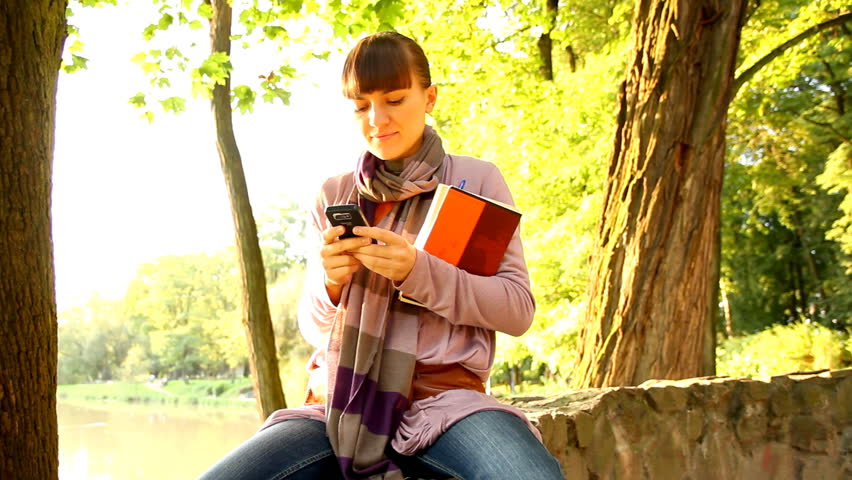 Female student sending sms and smiling at camera, outdoors - HD stock video clip