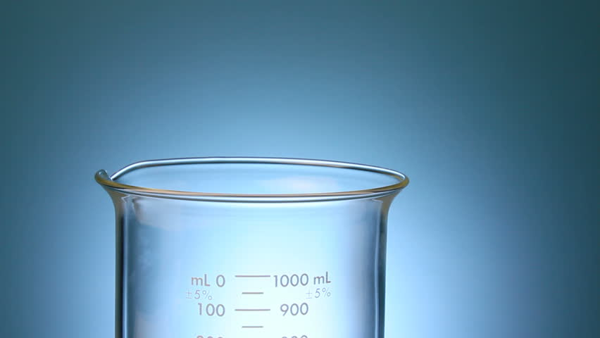 Refined oil being poured into a beaker from a container