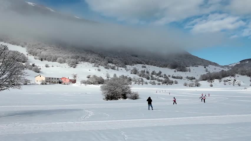 Video clip of children country-cross skiing in a single file and a man photographing them, Abruzzi, Italy.