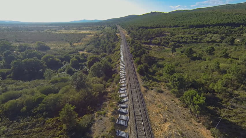 Train running forward over railway in the forest at sunset, heading forward, aerial view