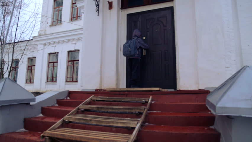 Caucasian boy near the building of the village school. A child walks and climbs near the old house. Country boy teenager. The boy sits near the closed school in the village. | Shutterstock HD Video #8829370