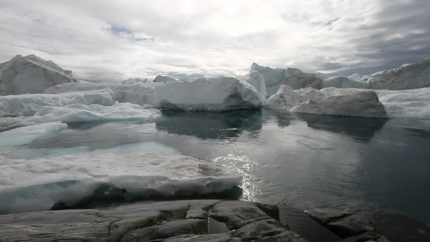 Calm moving water in front of some icebergs. This is the ice-fjord by Ilulissat, Greenland.  - HD stock footage clip