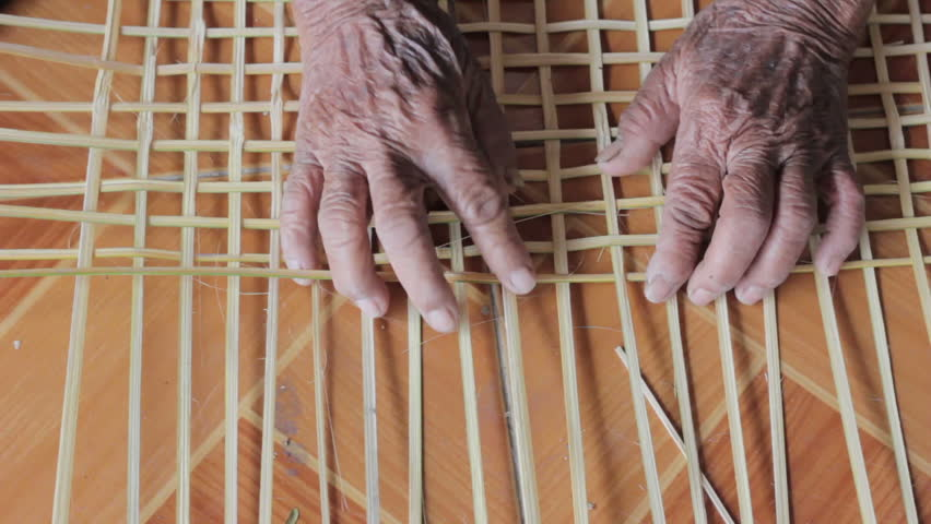 close-up hands of old woman weaving bamboo strips on the floor - HD stock video clip