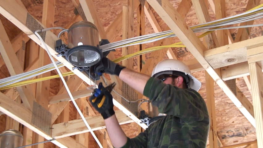 New home construction, electrician installing a ceiling light. Ambient audio included. - HD stock video clip