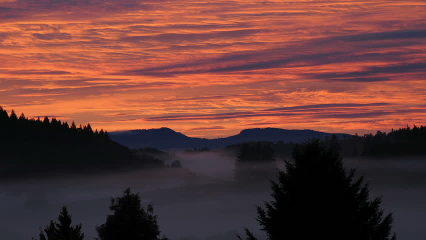 Timelapse footage of a landscape with morning fog coming around the mountains as day approaches. Beautiful pink and purple clouds above the sunrise - HD stock video clip
