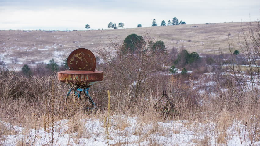 Abandoned farm equipment in overgrown grass. Rusty farm equipment in overgrown dried grass on depressed day. - HD stock video clip