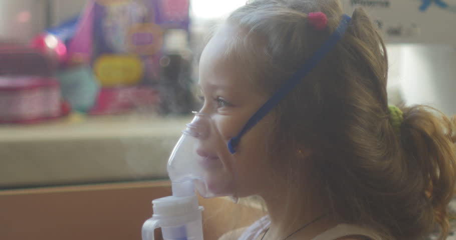 Girl sitting in bed in the hospital and inhales. The girl is sick, coughing, sad, not funny, treatment in the hospital, at the doctor's. Inhalation mask on her face. | Shutterstock HD Video #8911846