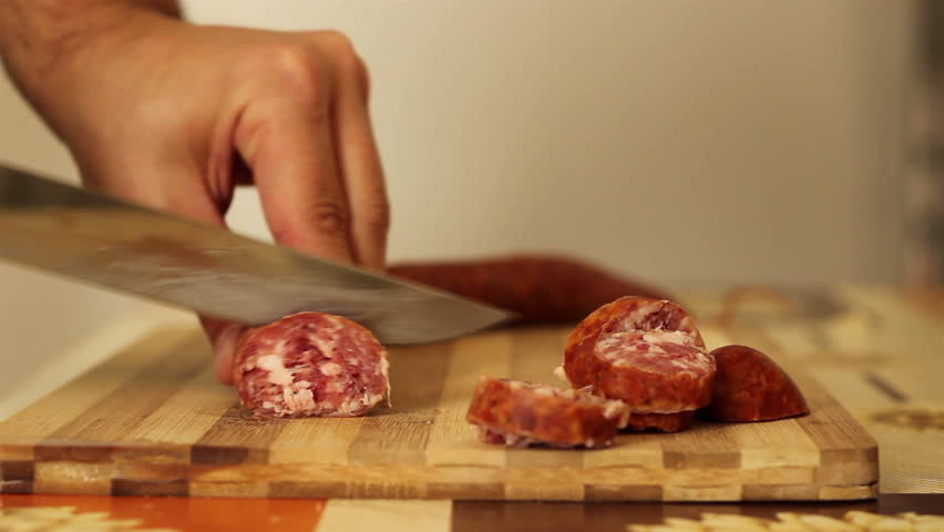 On a kitchen wood board, cook is slicing round homedate fresh sausage for meal. - HD stock video clip