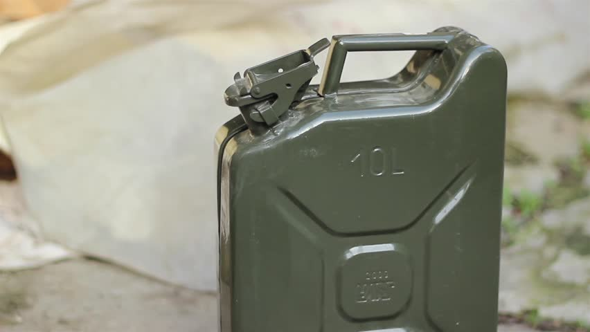 A person opens and pick up a petrol canister (jerry can)
