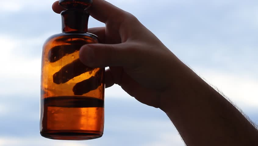Old mysterious liquid, on a thick handmade old brown bottle, is easily mixed by hand. Suitable video for antique chemistry, magic potions, cures, treatments or medicine, drugs preparations.