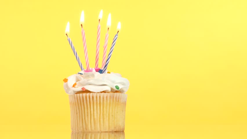 Tasty birthday cupcake with one candle, on yellow background
